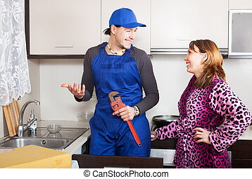 Handsome plumber talking with housewife