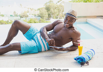 Handsome shirtless man using tablet pc poolside on a sunny...