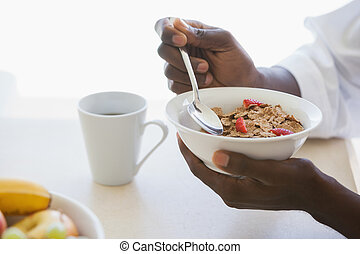 Man eating bowl of cereal outside