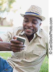 Smiling man relaxing in his garden texting on phone on a...