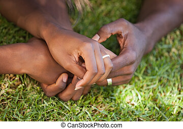 Couple holding hands on the grass