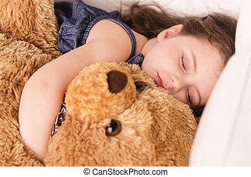 little girl hugging teddy bear closeup view of nice girl...