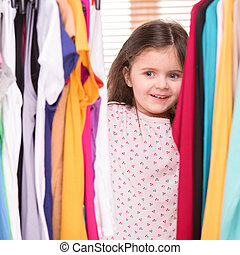amazed little girl looking at clothes. nice girl choosing...