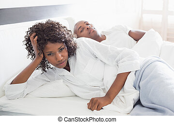 Annoyed woman lying in bed with boyfriend at home in the...