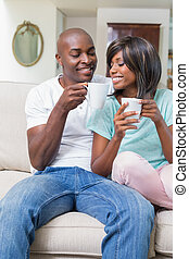 Happy couple relaxing on the couch having coffee at home in...