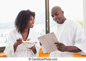 Happy couple having breakfast together in bathrobes at home...