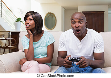 Bored woman sitting next to her boyfriend playing video...