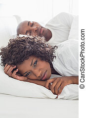 Upset woman lying in bed with sleeping boyfriend at home in...