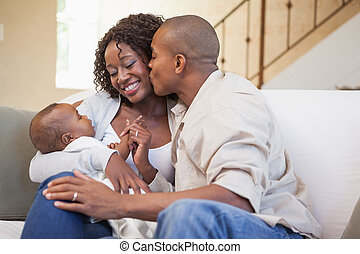Happy parents spending time with baby on the couch at home...