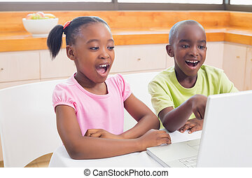Cute siblings using laptop together at home in the kitchen