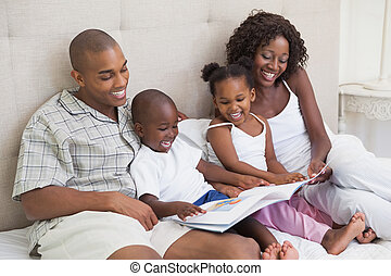 Happy family lying on bed reading book at home in the...