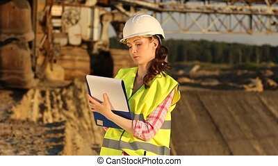Pretty woman with drawing on excavator background
