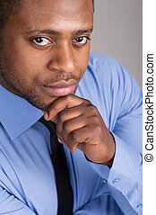 good looking black man thinking. handsome man folded hands...