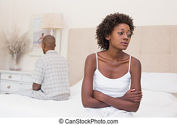 Unhappy couple not speaking to each other on bed at home in...