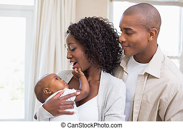 Happy young parents spending time with baby at home in the...