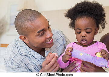 Happy parents playing with baby girl on bed together