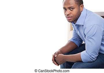 handsome black male in blue shirt. Attractive man on couch...