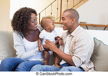 Happy young parents spending time with baby on the couch at...