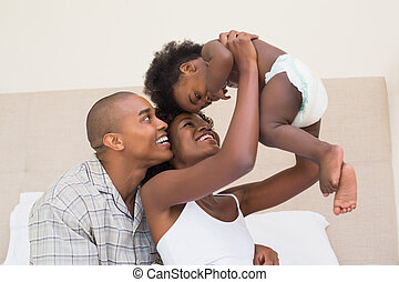 Happy couple on bed with baby daughter at home in the...