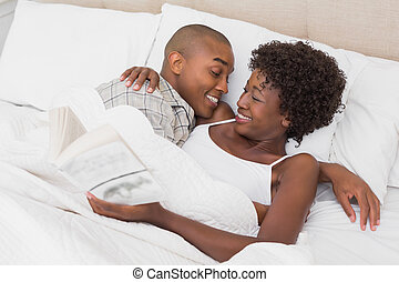 Happy couple lying in bed cuddling at home in the bedroom