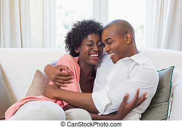 Happy couple relaxing on the couch at home in the living...