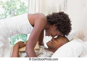Intimate couple messing about in the morning on bed at home...