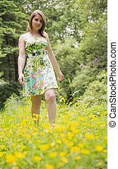Cute young woman standing in field