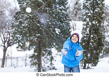 schoolboy playing outside and throwing snowballs. child...