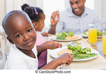 Family enjoying a healthy meal together with son smiling at...