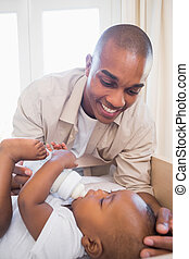 Happy father playing with his baby son in crib at home in...