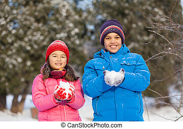 boy and girl holding snow and smiling. two children looking...