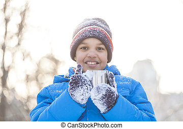 boy holding cup of hot tea. boy wearing winter blue jacket