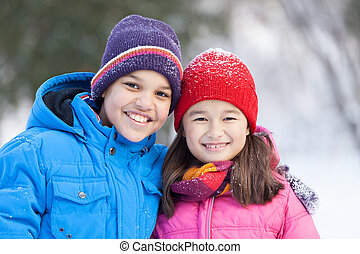 sister and brother smiling and hugging outside. boy and girl standing in park and looking into camera