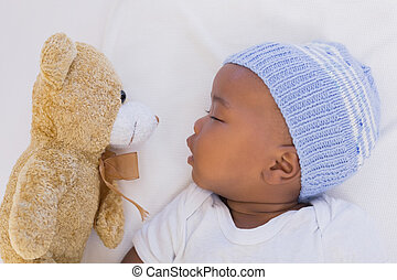 Adorable baby boy sleeping peacefully with teddy at home in...