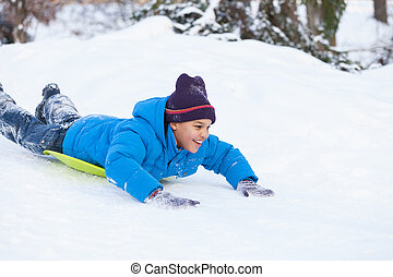 boy lying on sledges and sliding down hill. child speeding...