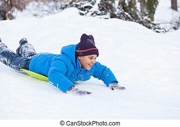 boy lying on sledges and sliding down hill. child speeding...