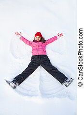 young girl laying on snow and making angel. child smiling and spreading hands and feet