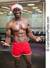 Shirtless macho man in santa hat at the gym - Portrait of...