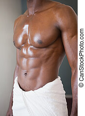 Mid section of a muscular man in white towel - Close-up mid...