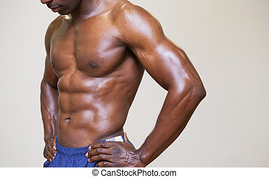 Close-up mid section of a shirtless muscular man over white...