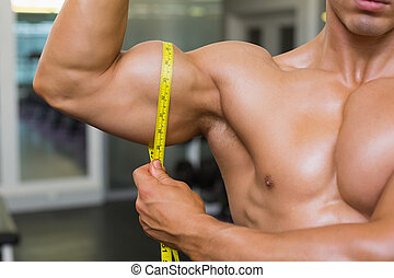 <id section of muscular man measuring biceps - Close-up...