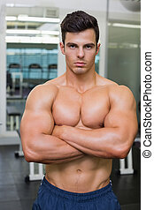 Serious young muscular man in gym - Serious shirtless young...