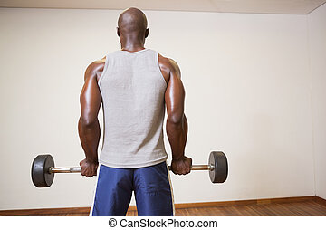 Rear view of a muscular man lifting barbell