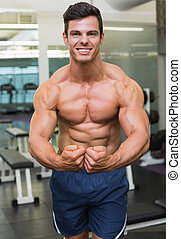 Shirtless muscular man flexing muscles in gym - Portrait of...