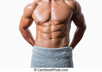 Mid section of a shirtless muscular man wrapped in white...