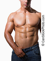 Mid section of a shirtless muscular man over white...