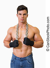 Portrait of a serious shirtless young muscular man over...