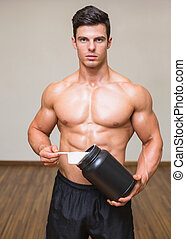 Body builder holding a scoop of protein mix in gym -...