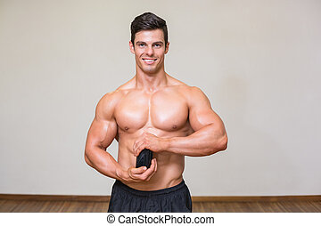 Body builder holding bottle with supplements in gym -...