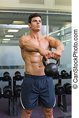 Muscular man lifting kettle bell in gym - Portrait of a...